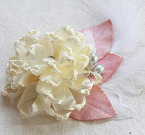 A Fabric Flower Fascinator with peach millinery leaves and a feather
