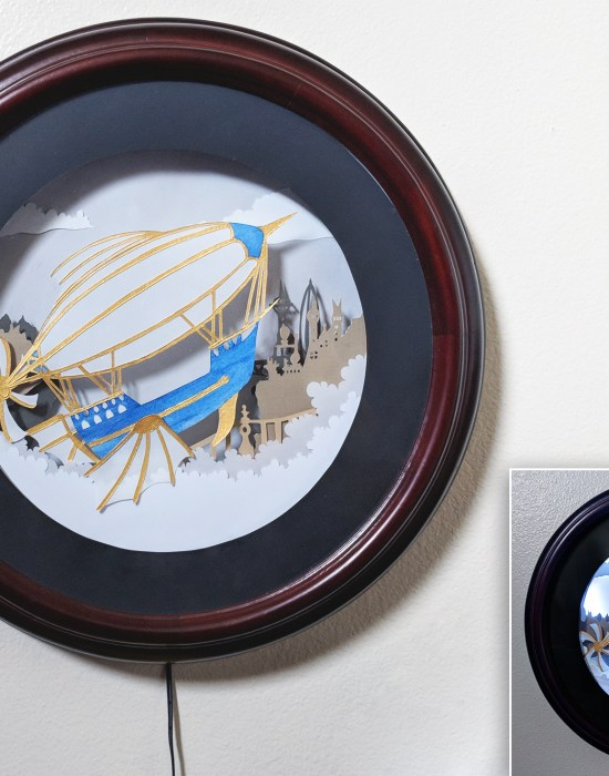 A hand cut paper art steampunk air ship with a city in the background in acircular shadowbox frame.