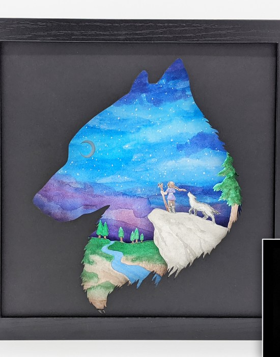 Hand cut paper art of a wolf and a girl standing on a rock looking out over a valley at the moon in the distance.