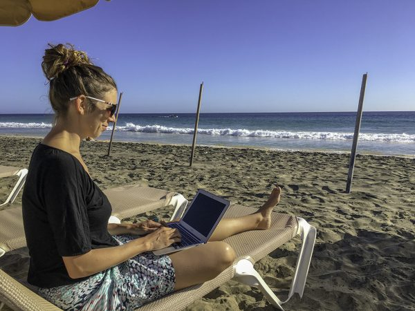 Digital nomad gadgets: working on my laptop at the beach in Fuerteventura