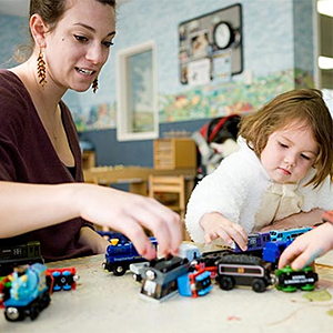 photo of young volunteer with child in playroom
