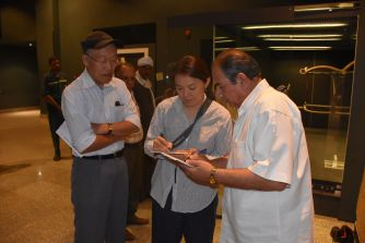 Ms. Nishisaka discussing with Mr. Nakamura and Mr. Osama the results of the artifacts condition