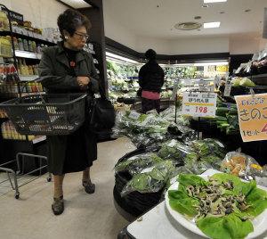 野菜売り場で商品を見て回る買い物客(東京)【AFP=時事】