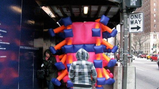 Jimmy Kuehnle squeezes under scaffolding in his inflatable suit