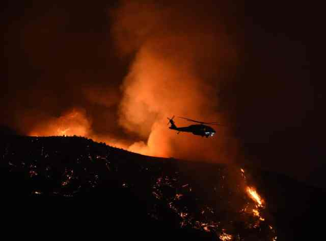 A firefighting helicopter makes a drop at Fair Oaks Canyon during the Sand Fire in Santa Clarita, California on July 24, 2016. Triple-digit temperatures and dry conditions are fueling the wildfire, which has burned across at least 22,000 acres so far and is only 10 percent contained. / AFP / Mark Ralston (Photo credit should read MARK RALSTON/AFP/Getty Images)