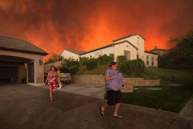 TOPSHOT - Residents flee their home as flames from the Sand Fire close in on July 23 2016 near Santa Clarita, California. Fueled by temperatures reaching about 108 degrees fahrenheit, the wildfire began yesterday has grown to 11,000 acres. / AFP / DAVID MCNEW (Photo credit should read DAVID MCNEW/AFP/Getty Images)