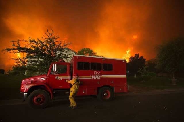 A firefighter reaches for the door of his truck as flames close in on homes at the Sand Fire on July 23 2016 near Santa Clarita, California. Fueled by temperatures reaching about 108 degrees fahrenheit, the wildfire began yesterday has grown to 11,000 acres. / AFP / DAVID MCNEW (Photo credit should read DAVID MCNEW/AFP/Getty Images)