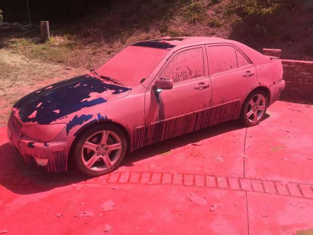 A car covered in aerially-applied fire retardant remains parked in Ruthspring Dr., in Santa Clarita, Calif., on Sunday, July 24, 2016. Two massive wildfires raged in tinder-dry California hills and canyons Sunday, leaving thousands of homes evacuated and authorities to investigate a burned body found in a neighborhood swept by flames. Firefighters have been trying to beat back a fire since Friday that has blackened more than 34 square miles of brush on ridgelines near the city of Santa Clarita and the Angeles National Forest. (AP Photo/Matt Hartman)