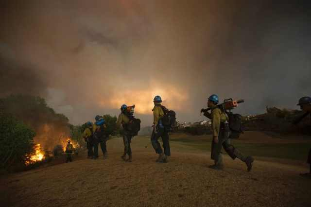 Firefighters of the Texas Canyon Hotshot crew fight the Sand Fire at a residential golf course on July 23 2016 near Santa Clarita, California. Fueled by temperatures reaching about 108 degrees fahrenheit, the wildfire began yesterday has grown to 11,000 acres. / AFP / DAVID MCNEW (Photo credit should read DAVID MCNEW/AFP/Getty Images)
