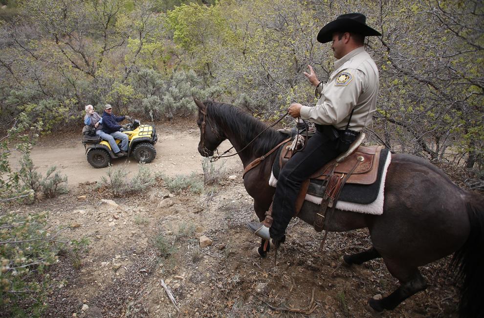 ATV riders drive past Kane County Sheriff deputy Rob Johnson