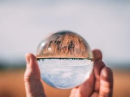 Skleněná koule v ruce s obráceným světem vzhůru nohama.
