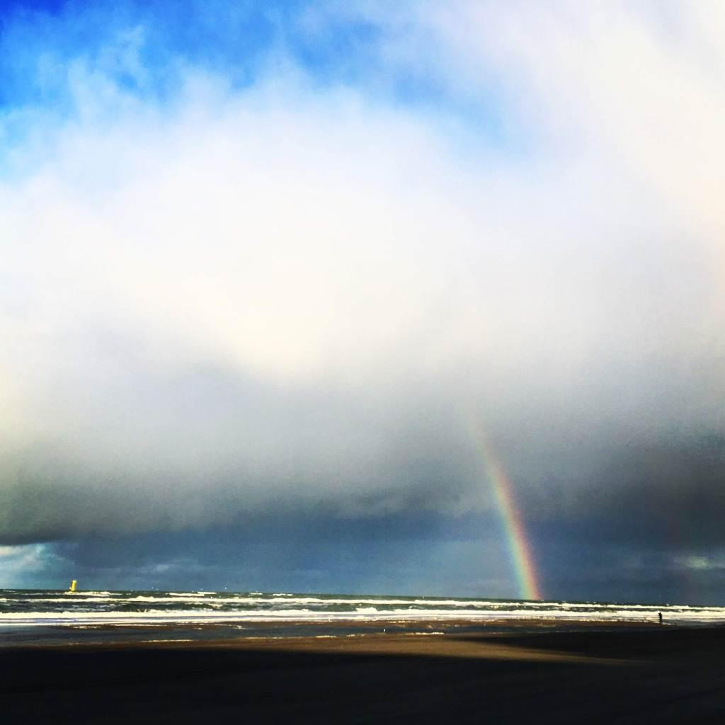 Een foto met regenboog met wolken, strand en de zee en op het Noordzeestrand bij De Koog, Texel, Nederland.