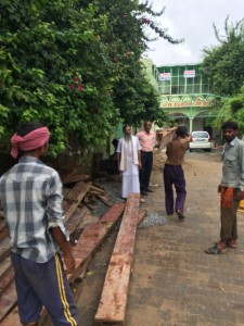 Babaji motivating a laborer to carry the heavy wood