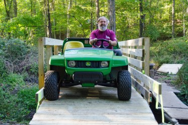 Volunteer and Bridge designer Mike Surdej drives the gator over the bridge the first time.