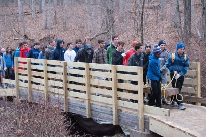 Members of the John Jay Track & Field team hauling one of the four 800 lb beams over bridge #1 to the site of bridge #2