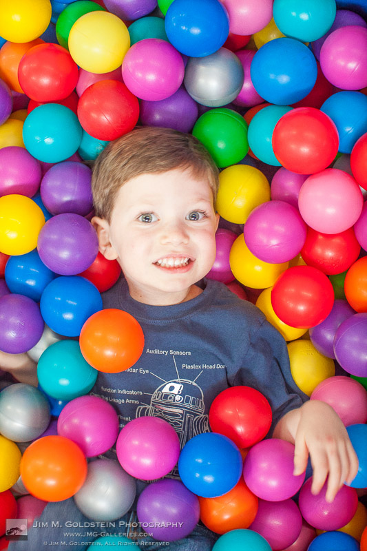 5 year old celebrating a birthday in a colorful plastic ball pit