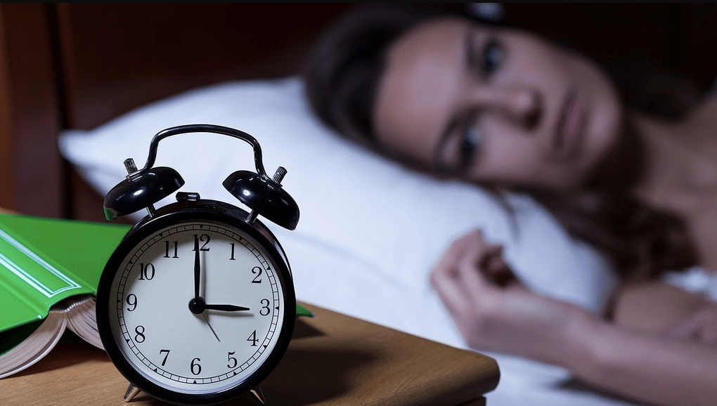 alarm clock next to a woman who can't sleep.