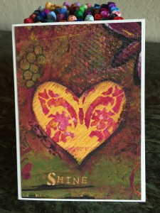 "this is a greeting card, 5x7, with a reproduction of a collage containing a heart in the center with a butterfly overlaw with the wod ""Shine"" below the heart"