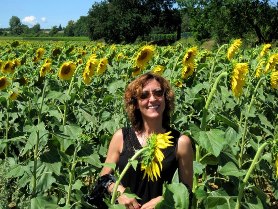 Joan Jakel standing in a field of sunflowers in Florence Italy where she celebrated stepping into her inspired life and used her experiences to launch the Create Your Inspired Life program.