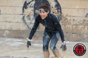 A photo of Joan Jakel mid Spartan race as she comes out of sloppy water ready to take on the rest of the race