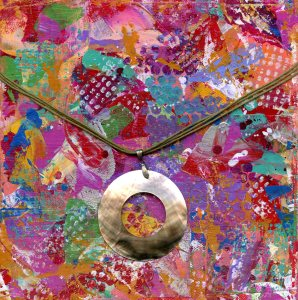 A colorful collage in pinks, burgundy, yellow, orange, blue, green, purple and yellow. A round pearlescent pendant hangs in the center from brown cords.