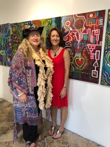An image of Joan Jakel and Shiloh Sopha standing next to one of Joan's paintings