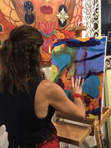 An image of Denise Beringer painting an abstract painting with her fingers