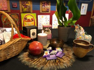 an image of a basket, pomegranate, cupt of tea, chocolate bars, an orchid and a lit candle on a round mat made of feathers