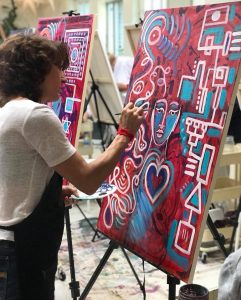An image of joan jakel at her canvas on an easel painting