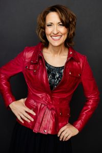 A photo of Joan Jakel wearing black lace top under a red leather jacket with her hands playfully on her waist and hip with a huge smile wearing red lipstick