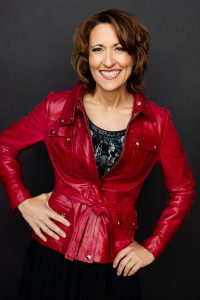 A photo of Joan Jakel wearing black lace top under a red leather jacket with her hands playfully on her waist and hip with a huge smile wearing read lipstick