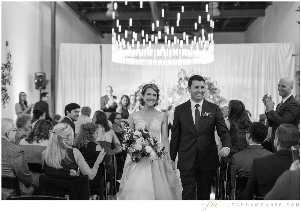 A bride and groom walk down the aisle during their elegant wedding at Canvas Event Space in SODO, Seattle, WA. | Joanna Monger Photography | Snohomish & Seattle Wedding Photographer