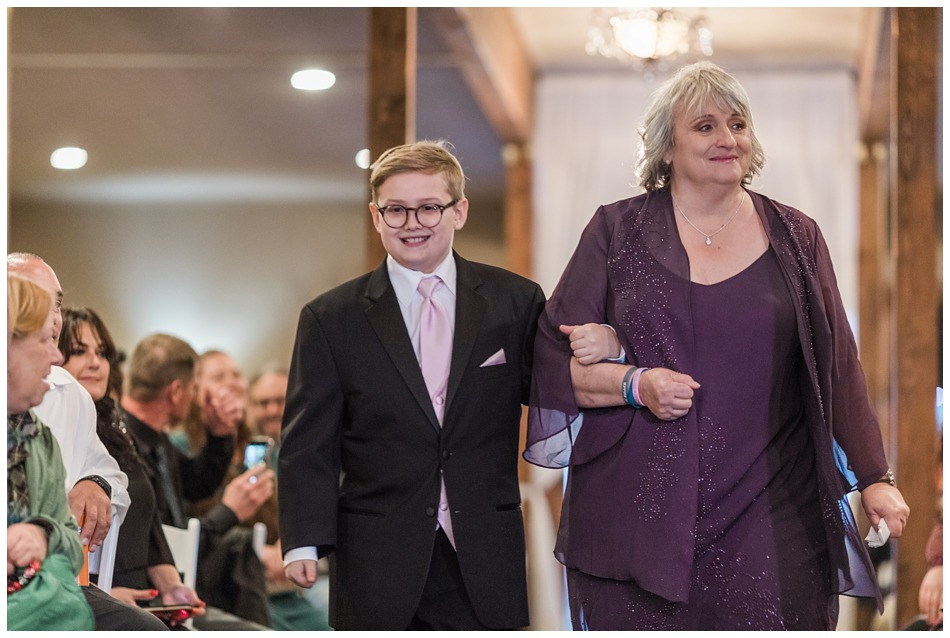The bride's son is accompanied down the aisle during the reception of her special winter wedding at Hidden Meadows, a wedding venue in Snohomish near Seattle, WA. | Joanna Monger Photography | Snohomish & Seattle Wedding Photography