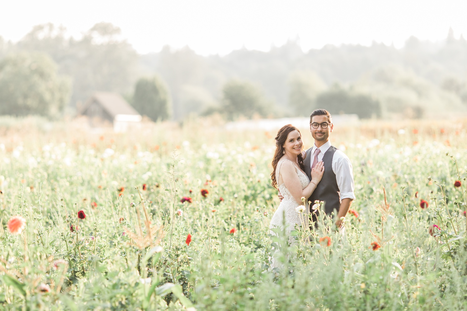A bride and groom embrace while standing in a field of flowers before their wedding at Woodland Meadow Farms in Snohomish, a wedding venue near Seattle, WA. | Joanna Monger Photography | Seattle & Snohomish Photographer