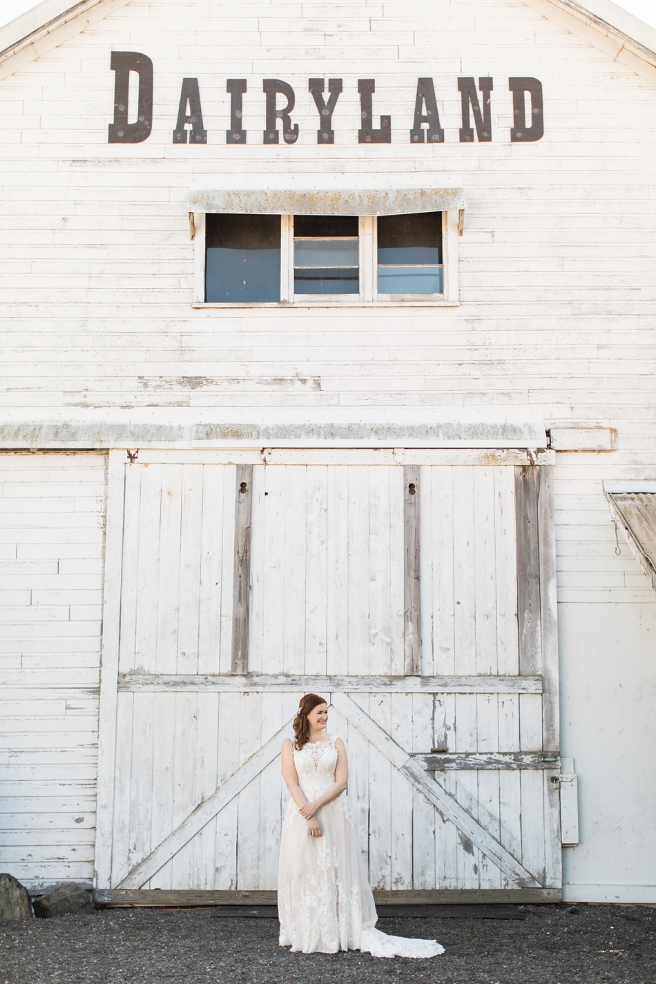 Bride Kate in her wedding dress, standing in front of a white-washed barn at Dairyland wedding venue in Snohomish, WA. | Joanna Monger Photography
