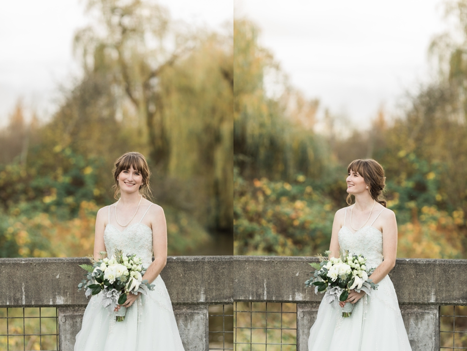 A bride smiles while holding her bouquet and standing on a concrete bridge before her fall wedding at the Loft at Russell's in Bothell, a wedding venue near Seattle. | Joanna Monger Photography | Snohomish & Seattle Wedding Photographer