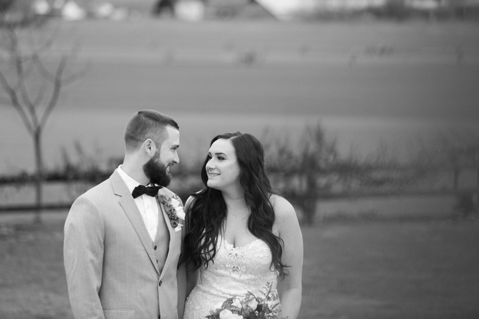 A black and white photo of a bride and groom lovingly looking at each other before their winter wedding at Hidden Meadows in Snohomish, a wedding venue near Seattle, WA. | Joanna Monger Photography | Snohomish & Seattle Wedding Photographer