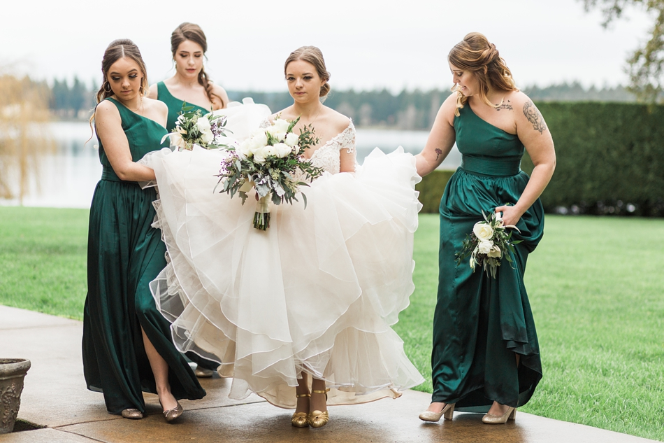 Bridesmaids hold the bottom of a bride's dress before her regal winter wedding at Thornewood Castle in Lakewood, a wedding venue near Seattle, WA. | Joanna Monger Photography | Seattle & Snohomish Wedding Photographer