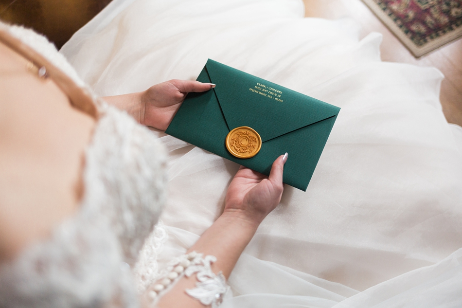 A bride holds a wax sealed envelope before her regal winter wedding at Thornewood Castle in Lakewood, a wedding venue near Seattle, WA. | Joanna Monger Photography | Seattle & Snohomish Wedding Photographer