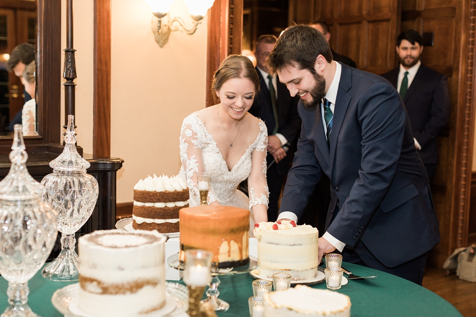 A bride and groom cut a cake from their regal winter wedding at Thornewood Castle in Lakewood, a wedding venue near Seattle, WA. | Joanna Monger Photography | Seattle & Snohomish Wedding Photographer