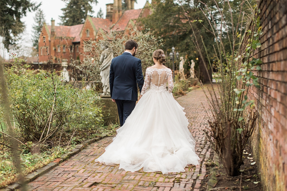 A bride and groom hold hands and walk down a brick path after their regal winter wedding at Thornewood Castle in Lakewood, a wedding venue near Seattle, WA. | Joanna Monger Photography | Seattle & Snohomish Wedding Photographer