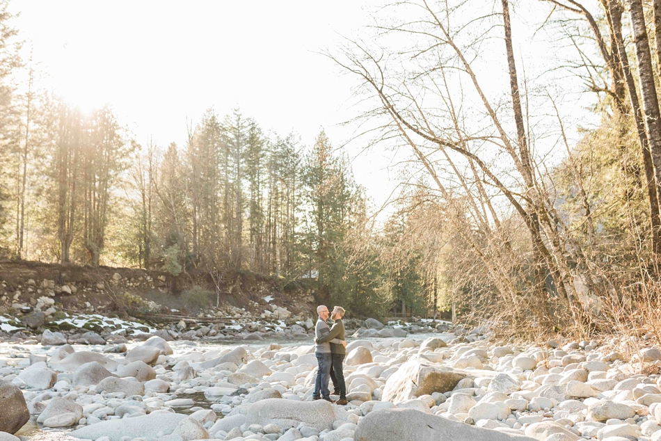 An engaged couple stand near a river during their spring outdoor mountain engagement shoot in Snohomish, near Seattle, WA. | Joanna Monger Photography | Snohomish Wedding Photographer