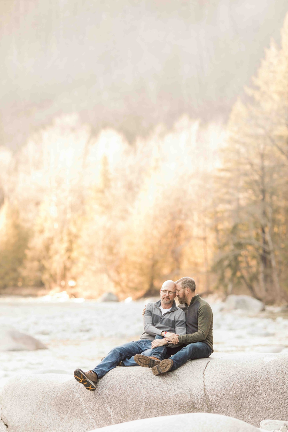 An engaged couple sit by a river during their spring outdoor mountain engagement shoot in Snohomish, near Seattle, WA. | Joanna Monger Photography | Snohomish Wedding Photographer