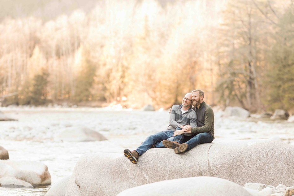 A couple sits by a river during their spring outdoor mountain engagement shoot in Snohomish, near Seattle, WA. | Joanna Monger Photography | Snohomish Wedding Photographer