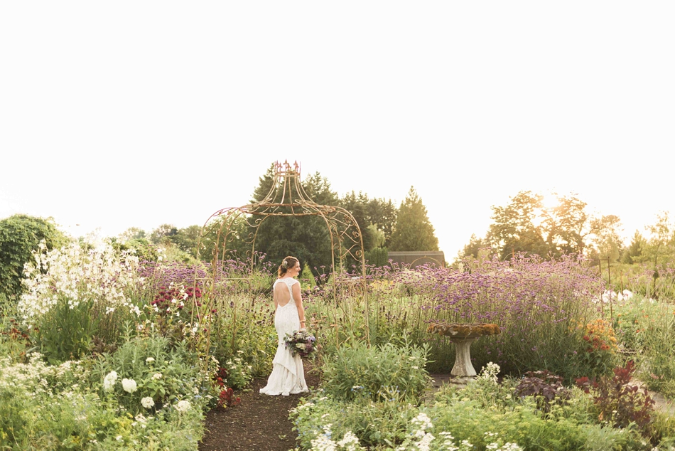 The bride looks out at a path at Pine Creek Nursery in Monroe. Photos by Joanna Monger Photography, Snohomish and Seattle Wedding Photographer.
