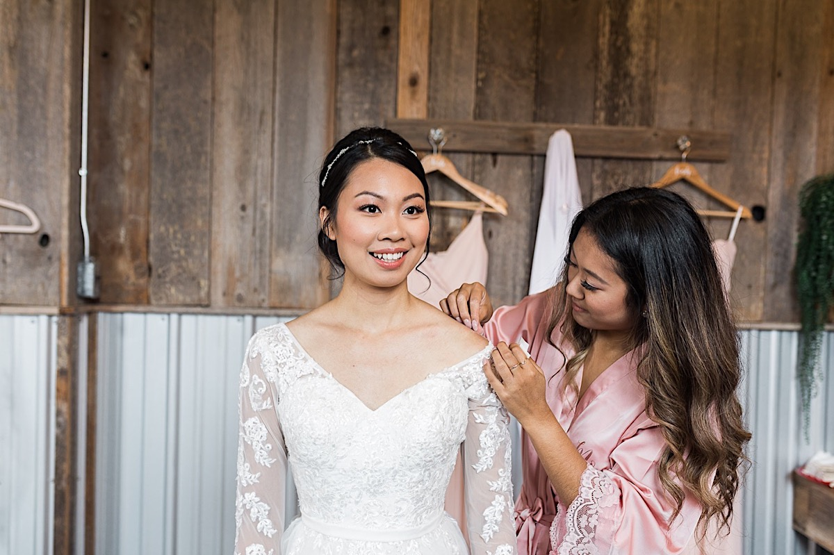 Bridesmaid helps adjust the dress at Craven Farms in Snohomish. Photographs by Joanna Monger Photography, Snohomish's Best Wedding Photographer.