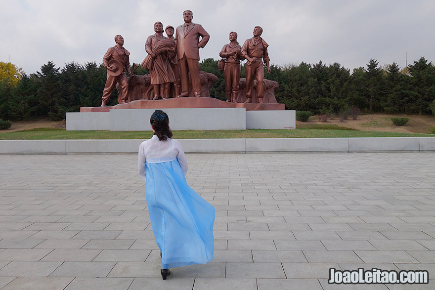 Woman with a traditional Korean blue dress and statues with the past leader Kim Il Sung.