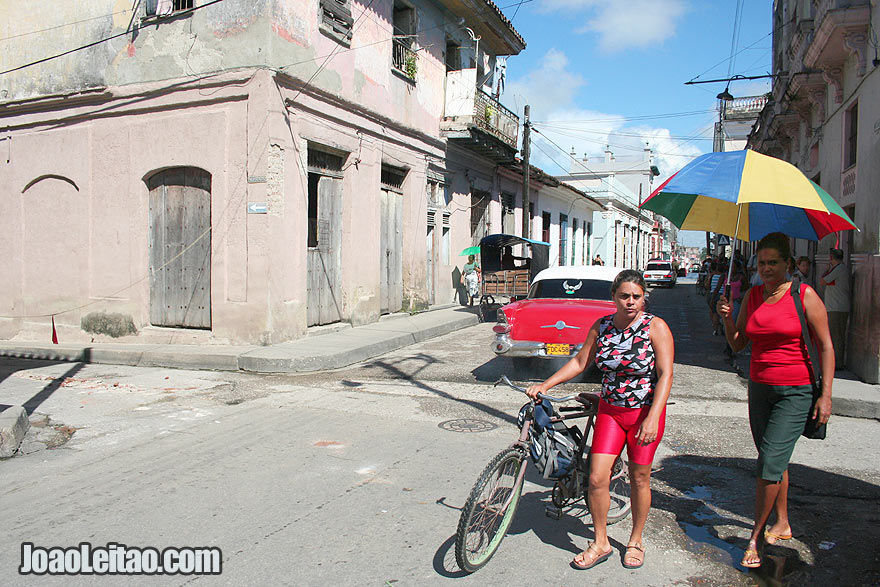 Remedios Street scene with red car and woman on a bicycle