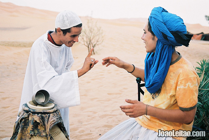 Photo of young men talking to each other in Erg Chebbi Dunes, Morocco