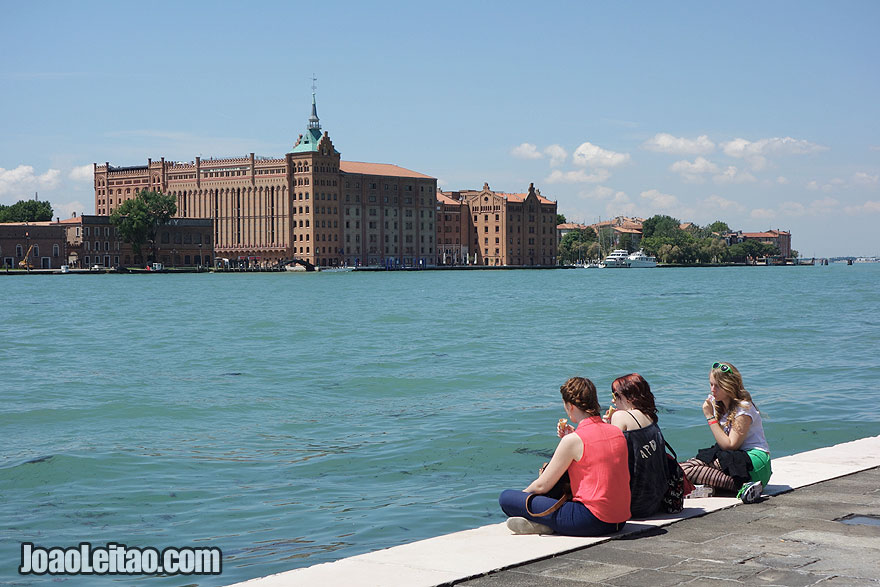 Girls overlooking Venice canals with Hotel Hilton Molino Stucky Venice located on Giudecca Island